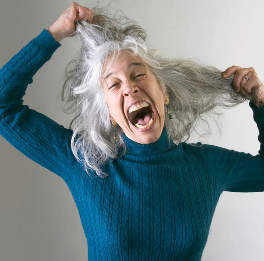 Женщина пытается выдернуть седые волосы
