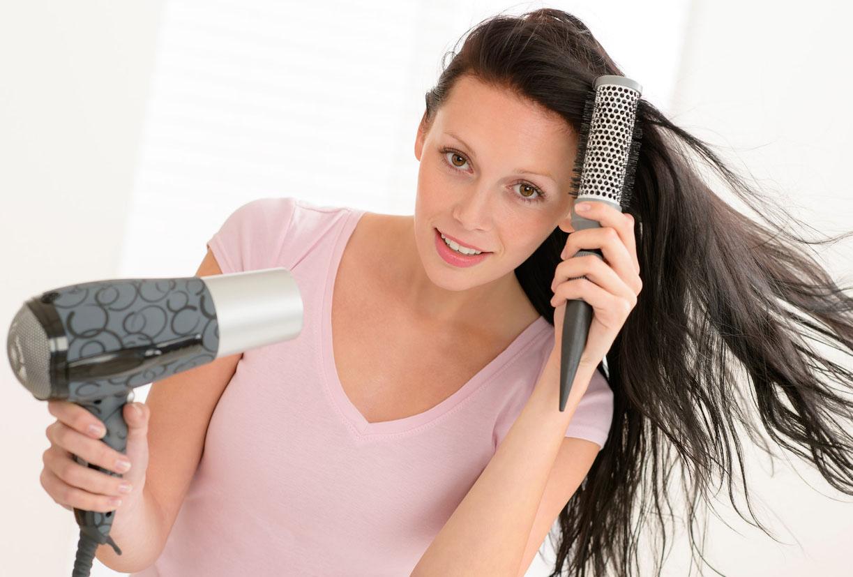 Девушка сушит волосы
