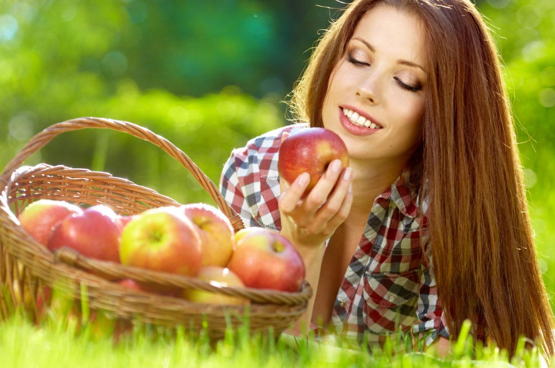 Девушка с яблоком на траве фото
