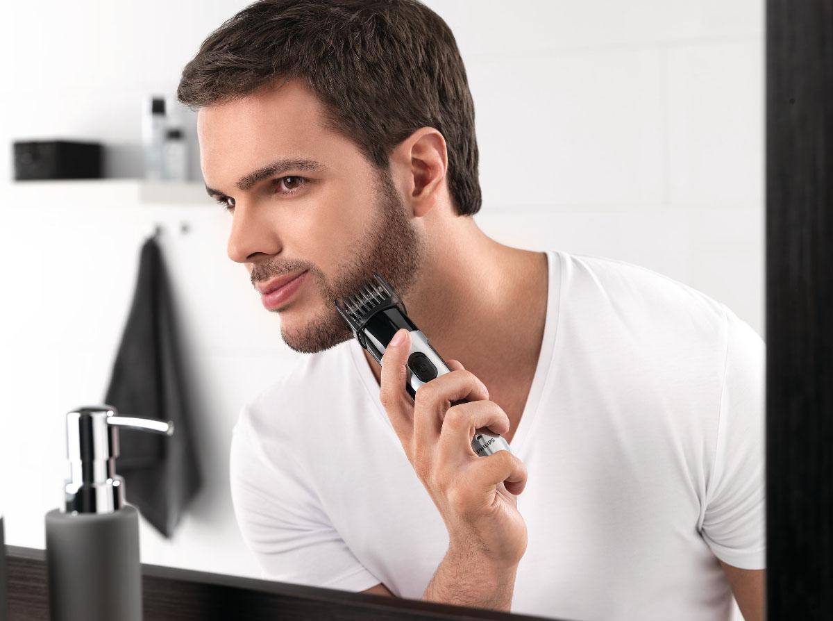 Мужчина подстригает бороду триммером