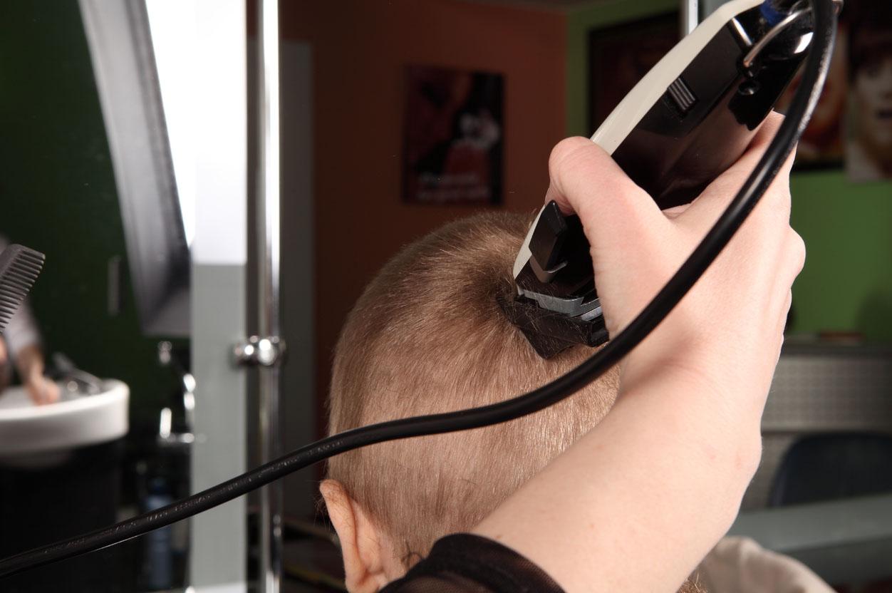 Стилист подстригает машинкой