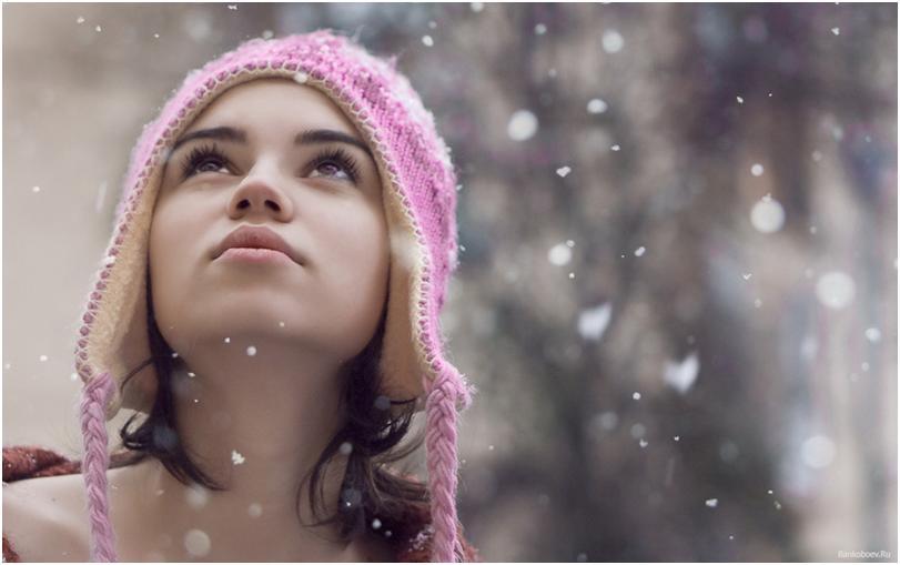 Девушка в шапке смотрит на снег