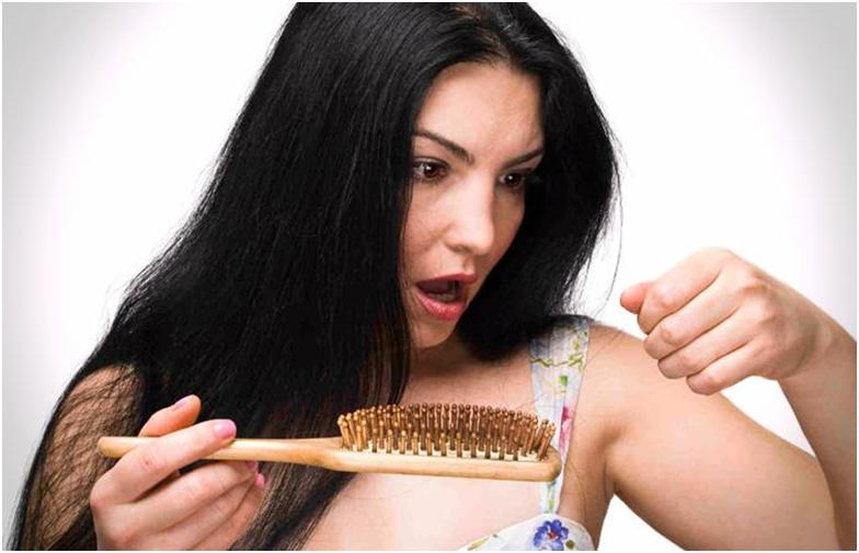 Возмущенная черноволосая девушка с волосами на расческе