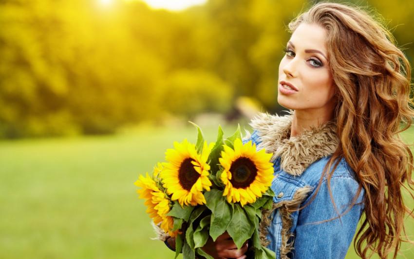 Девушка со светлыми, длинными, волнистыми волосами и с букетом подсолнухов