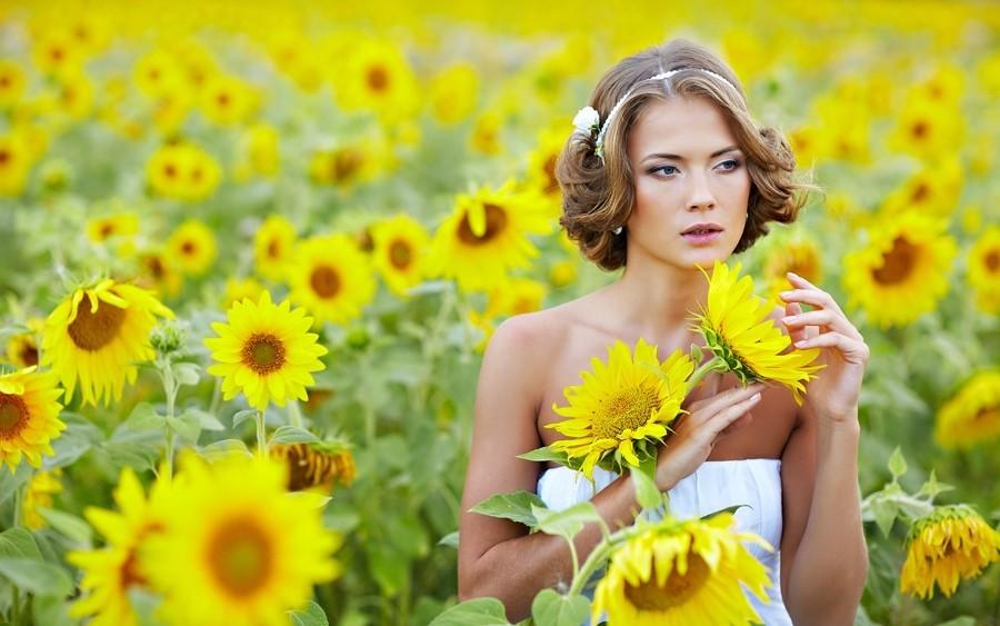 Девушка со светлыми волосами в поле с подсолнухами
