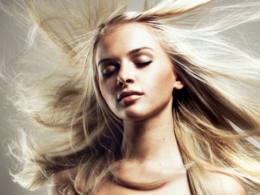 Девушка с длинными, светлыми, развивающимися волосами и закрытыми глазами