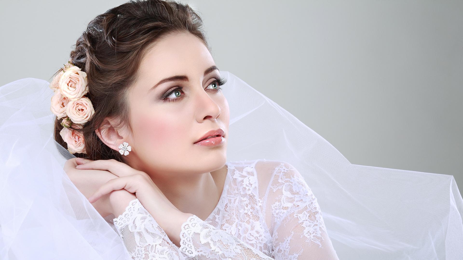 Невеста с красивой прической, фатой и цветами в волосах