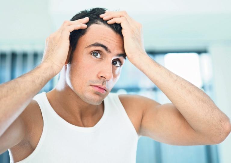 Мужчина в майке рассматривает свои волосы