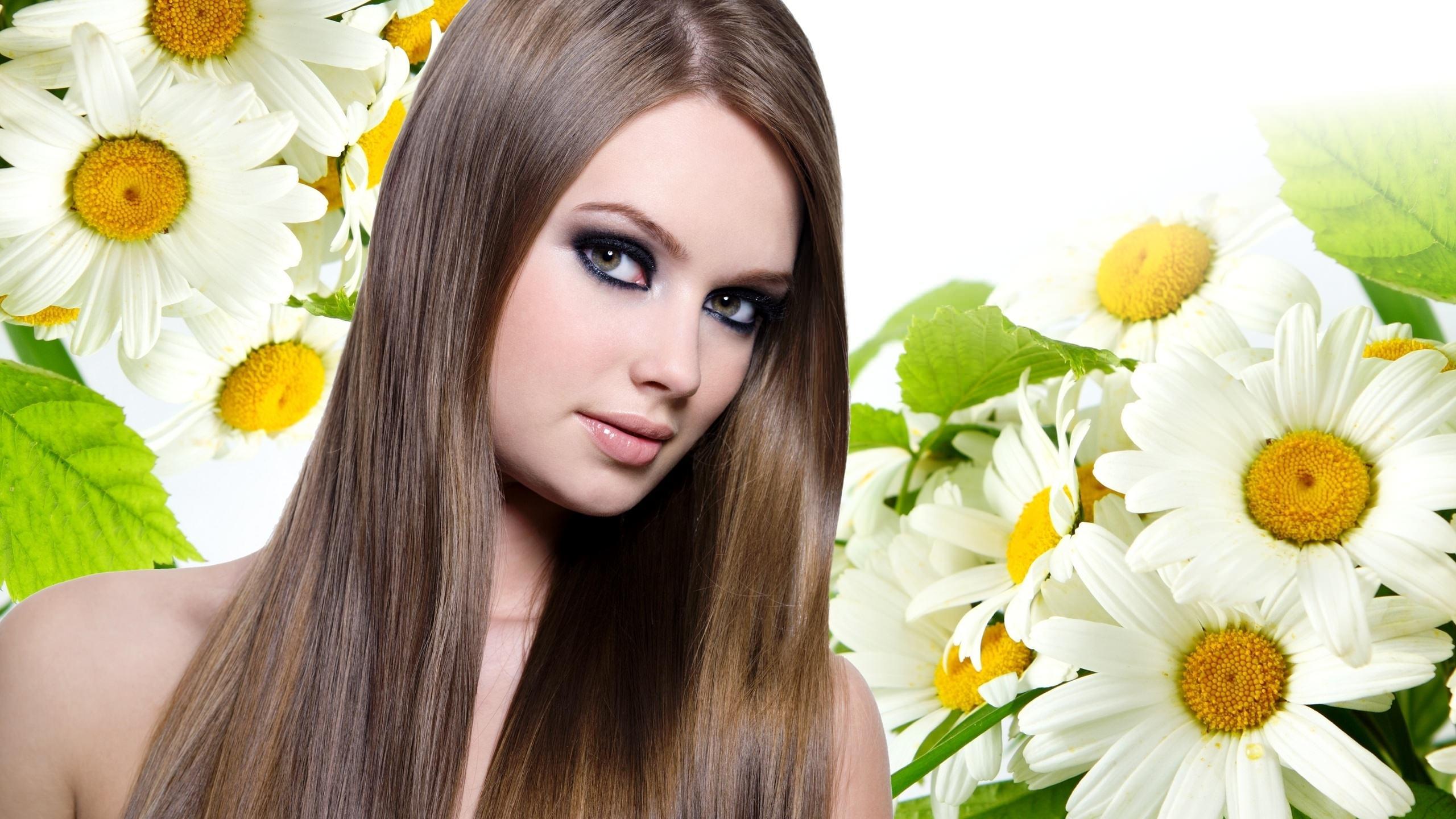 Девушка с русыми, длинными, прямыми волосами на фоне ромашек