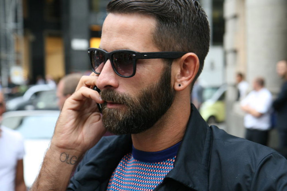 Мужчина с бородой в очках разговаривает по телефону