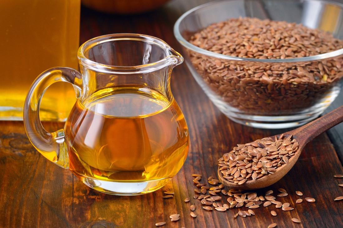 Льняное масло в графине и семена льна в чашке