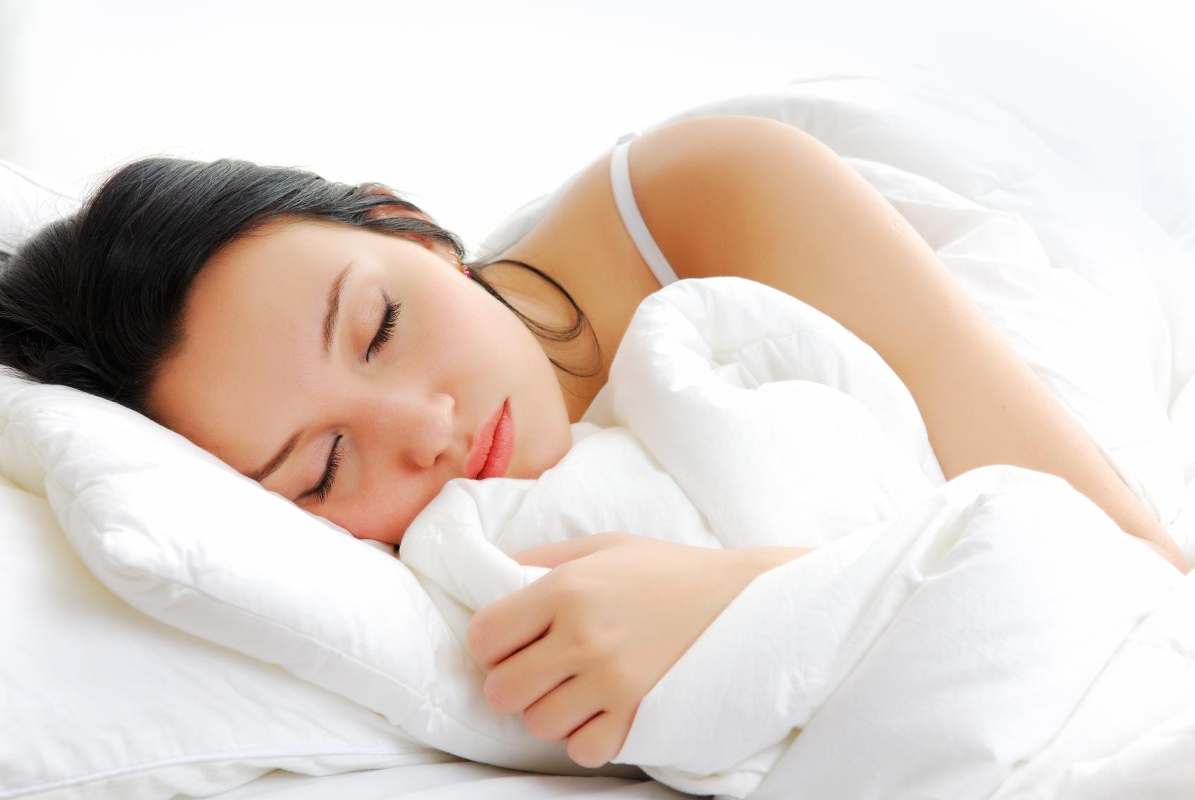 Спящая девушка на белом белье