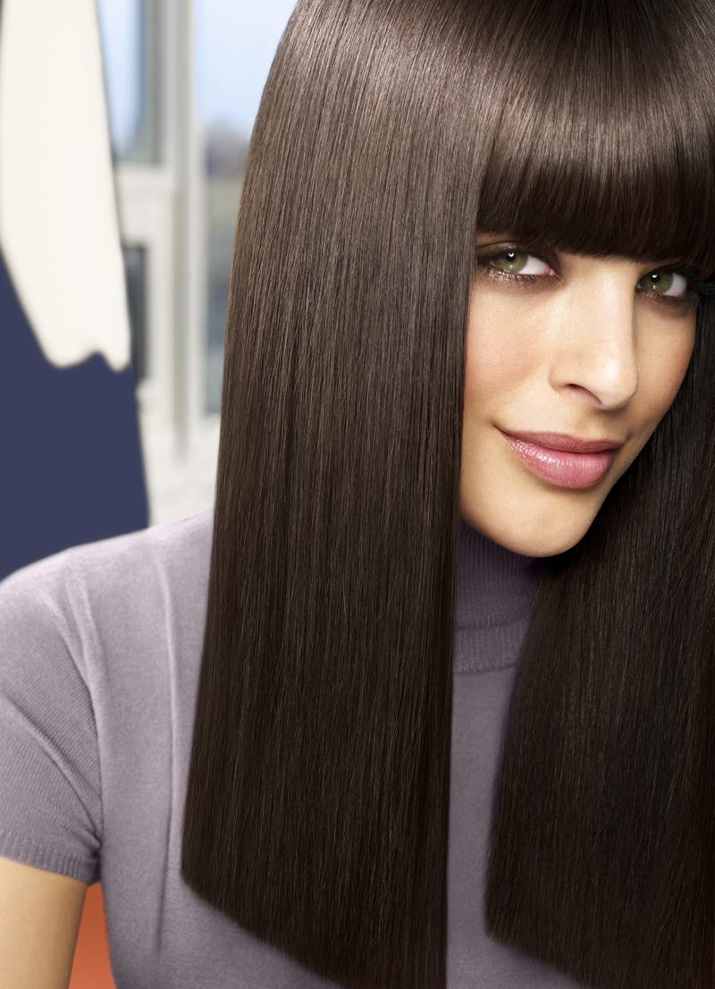 Девушка с прямыми темными волосами улыбается