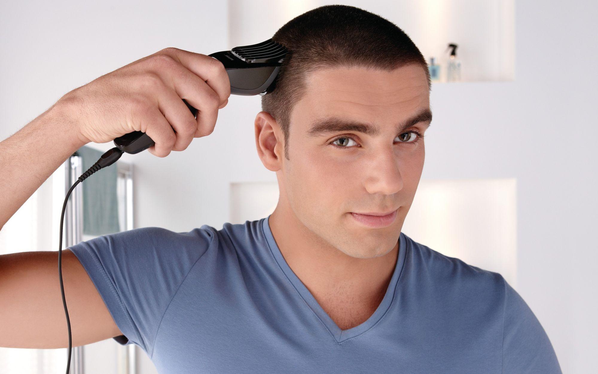 Мужчина подстригает волосы электрической машинкой