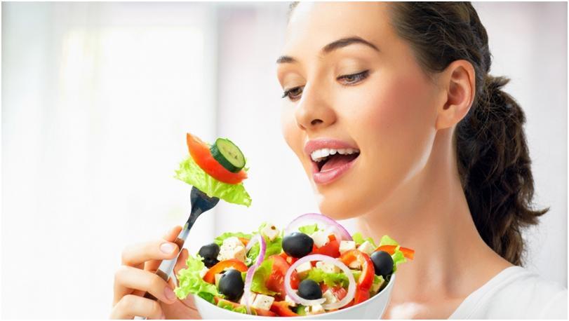 Девушка кушает овощи